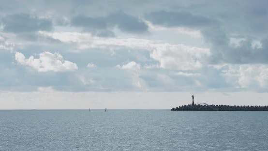Seagulls and Cormorants Sit on Breakwater. Lighthouse on Cloudy Sky Background. Port of Sochi