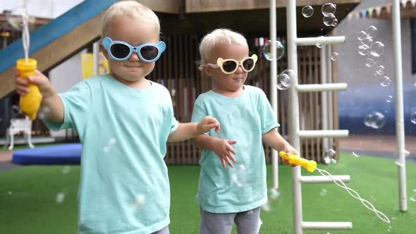 Cute Twin Girls Wearing Colourful Sunglasses Playing with Soap Bubbles