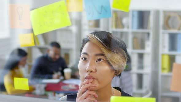 Thumbnail for Thoughtful Asian Woman Looking at Memos