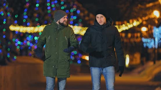 Man with a Beard Walks Down the Street with a Friend in Winter