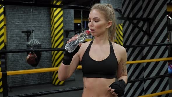 A Tired Girl Drinks Water Standing in the Boxing Ring