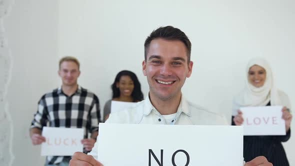 "Thumbnail for Young Man Posing on Camera with Poster with Words ""No Racism"""