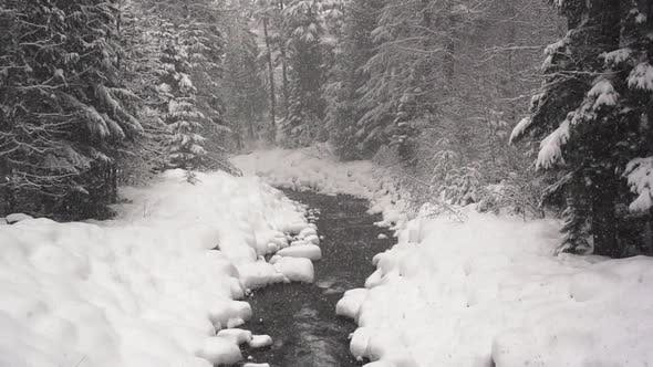 Thumbnail for Snow falls over a snow lined river
