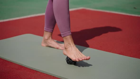 Exercise with Small Ball for Feet Woman is Rolling Ball By Bare Foot