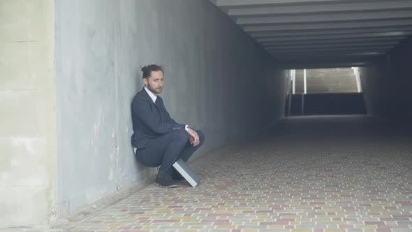 Thumbnail for Wide Shot of Depressed Man in Suit Sitting Against the Wall in Underground Crossing. Frustrated