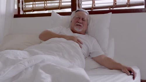 Elderly Asian man Heart pain due to heart disease in bed room.