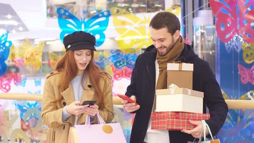 Cheerful Happy Married Couple Buy Gifts for Friends in Mall