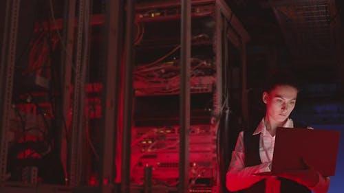 Businesswoman Using Laptop in Datacenter Room