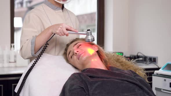 Beautiful Adult Blond Woman with Long Curly Hair Having Ultrasonic Cleaning in Spa Salon