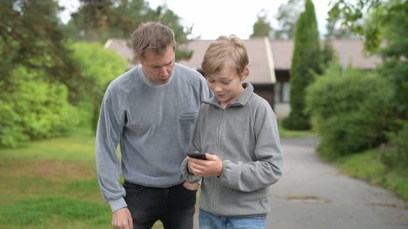 Cover Image for Young Handsome Man Using Phone With Young Boy Together At Home Outdoors