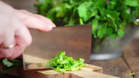 Hands Men Cut a Bundle of Fresh Parsley on a Cutting Board.