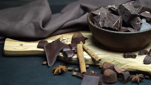 Cover Image for Dark or Milk Organic Chocolate Pieces and Truffle Candies in Wooden Bowl on Dark Concrete Background