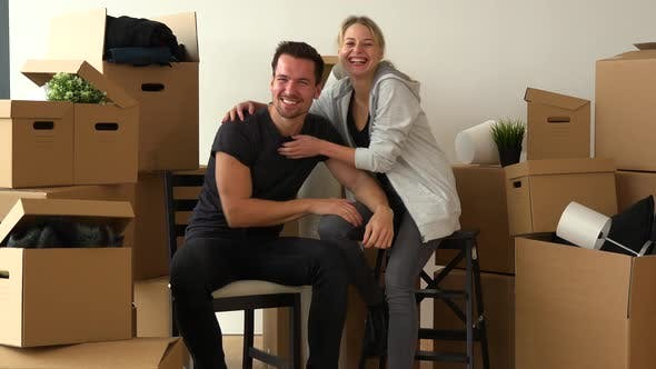 Thumbnail for A Happy Moving Couple Sits on Chairs, Looks at the Camera and Celebrates in an Empty Apartment