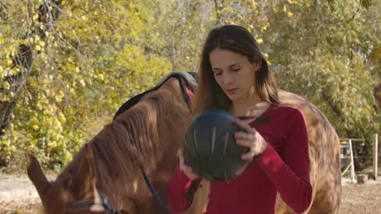 Cover Image for Professional Female Caucasian Jockey Putting on Horse Riding Helmet