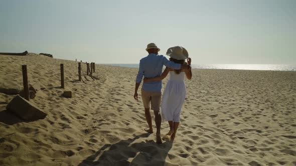 Thumbnail for Back View of Couple Walking on Sandy Beach
