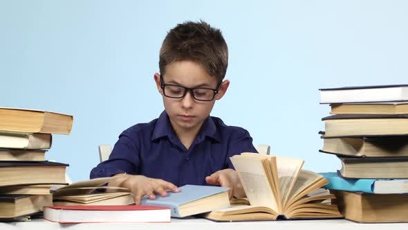 Boy Sits at the Table and Pull Up a Page with a Notebook. Blue Background.