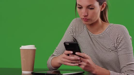 Thumbnail for Millennial woman sitting at cafe table texting with smartphone on greenscreen