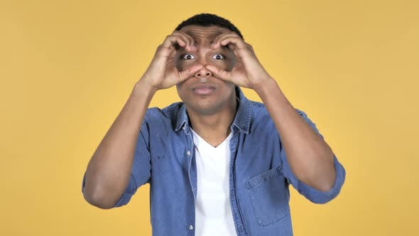 Cover Image for Young African Man Searching with Handmade Binoculars, Yellow Background
