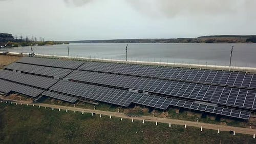 Aerial view of Solar panels near the river. Alternative source of electricity. Solar farm.