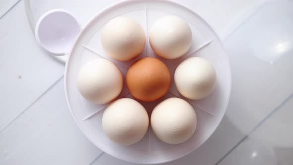 Thumbnail for Chicken Eggs in a Egg Electric Cooker on a White Wooden Table
