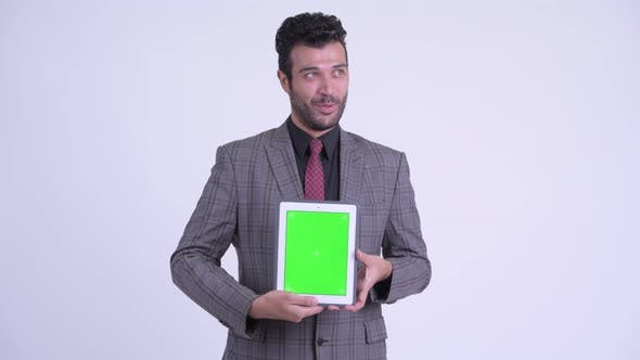Thumbnail for Happy Bearded Persian Businessman Thinking While Showing Digital Tablet