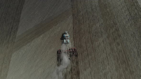 Thumbnail for A Tractor with a Harrow Cultivates the Land