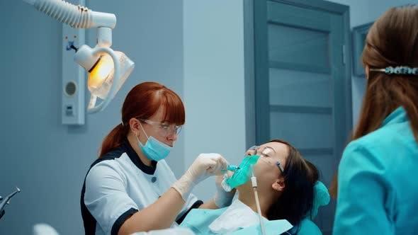 Girl having dental treatment. Woman having dental procedure at the dentistry clinic