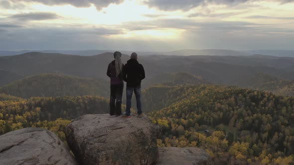A Young Couple Stand on Top of a Mountain and Enjoy the Sunset. Hikers on a High Cliff.