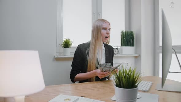Woman Celebrating Success in Office, Elegant Blond Female Sitting at Workplace Holding in Hands