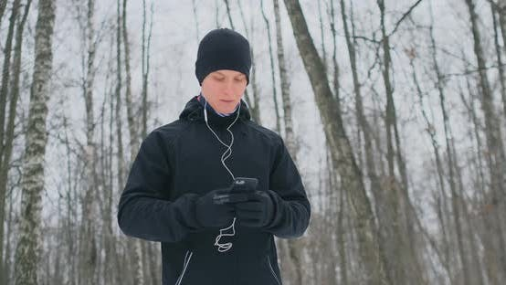 Thumbnail for A Young Man in a Black Hammer in the Winter Is Preparing To Jog in the Park Includes an Application