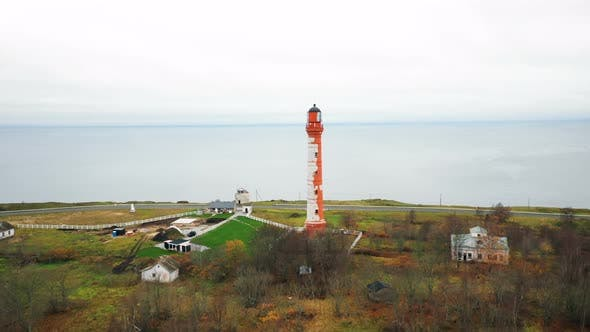Thumbnail for Beautiful Aerial Panning Shot of Scenic Old Lighthouse and Buildings on Picturesque Overcast Sea
