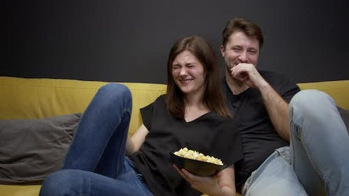 Attractive Young Couple Sitting on Sofa with Popcorn Watching Movie on TV