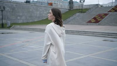 Beautiful Girl in a White Hoodie Walks Through an Empty City Alone