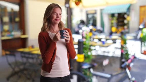 Portrait of calm relaxed woman drinking coffee outside