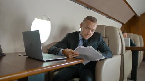 Handsome Businessman Working with Docs and Notebook in Private Jet