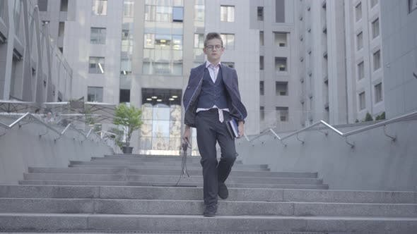 Cover Image for Serious Well-dressed Boy Walking Down the Street Pulling the Keyboard Along the Steps