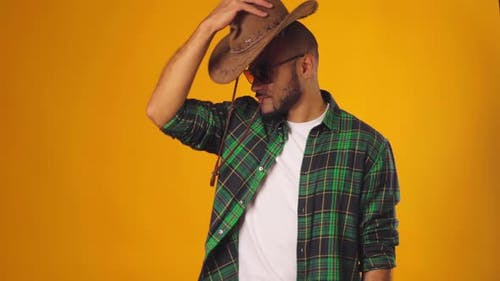 Handsome Young African American Man Putting on Cowboy Hat Against Yellow Background in Studio