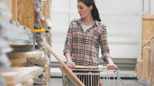 Mädchen 25 Jahre in einem Baumarkt mit einem Wagen kauft eine Säge