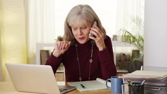 Thumbnail for Mature woman talking smartphone laptop computer