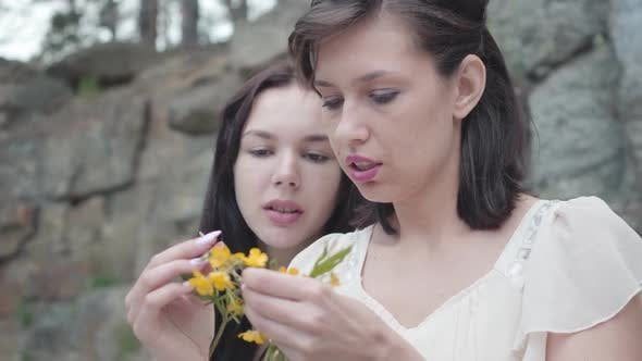 Thumbnail for Portrait Two Beautiful Women with Black Hair Braid Flower Crown Near Huge Stone with Green Plants