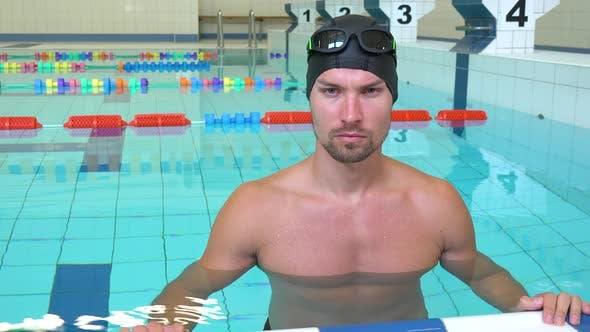 Thumbnail for Ein professioneller Schwimmer sieht ernsthaft an die Kamera am Rande eines Hallenpools - Nahaufnahme