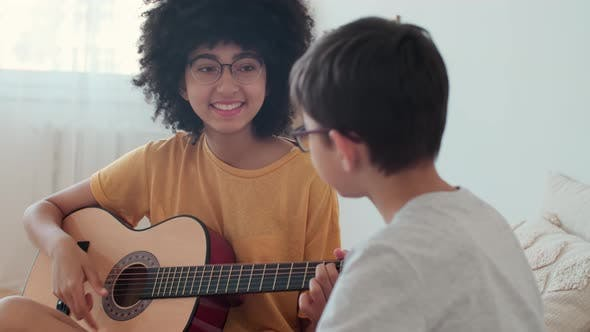 Afro American Girl Teacher Teaching Guitar Lessons to Teenager