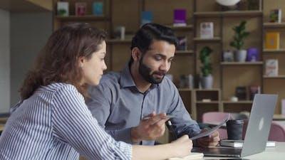 Indian Teacher or Mentor Helping Latin Student Teaching Intern Using Laptop