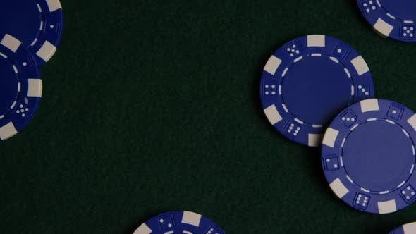 Rotating shot of poker cards and poker chips on a green felt surface - POKER 024