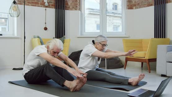 Senior Couple Stretching on Yoga Mats while Doing Workout when Watching Lessons on Laptop at Home