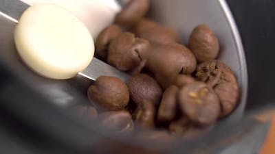 Arabic roasted coffee beans falling into an electric coffee grinder in slow motion