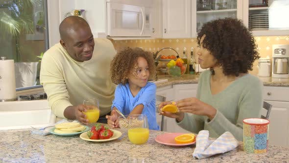 Thumbnail for African American family  being silly with food in kitchen
