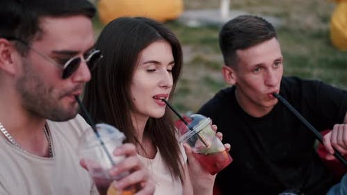 Two European Boys Are Smoking and a Girl Is Drinking a Cockta
