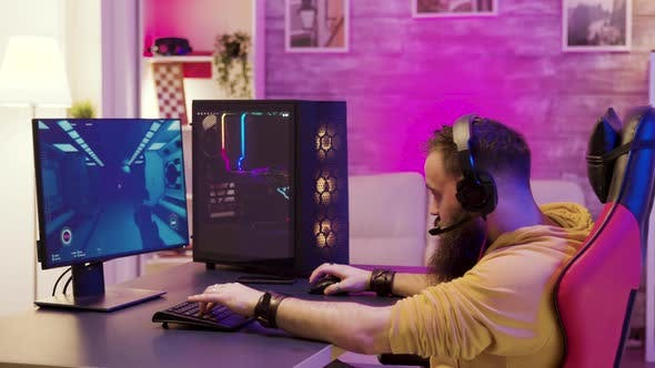 Bearded Man Playing Online Video Games on His Pc