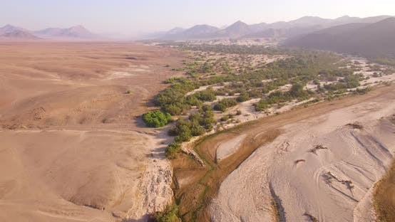 Dry Riverbed Next to Desert